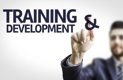 Business man pointing to transparent board with text Training & Development.jpeg